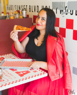 Amy Stretten Chief of Style at a pizza parlor in Hollywood, California wearing a red eloquii moto jacket and a red eloquii tuelle skirt