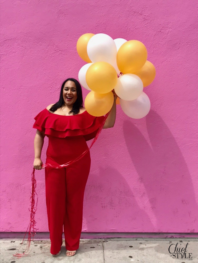 chief of style Amy Stretten in a birthday photo holding balloons in front of the Paul Smith wall on Melrose in a red plus size jumpsuit from fashion nova curve