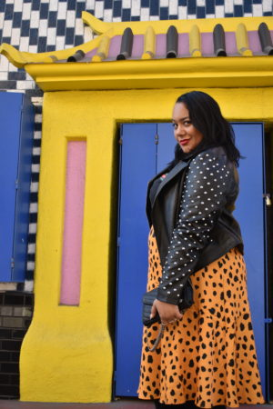 Amy Stretten, The Chief of Style, wearing a Forever 21+ studded leather jacket, femme t-shirt, eloquii by who what wear plus size satin skirt, charlotte russee plus suede boots and a YSL envelope shoulder bag