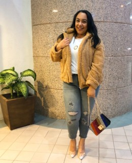 Plus size fashion blogger and journalist, Amy Stretten, aka The Chief of Style, wearing a teddybear coat, rhinestone embellished distressed skinny jeans from Lane Bryant, and clear heels while carrying a rhinestone encrusted rainbow purse in Sherman Oaks, California